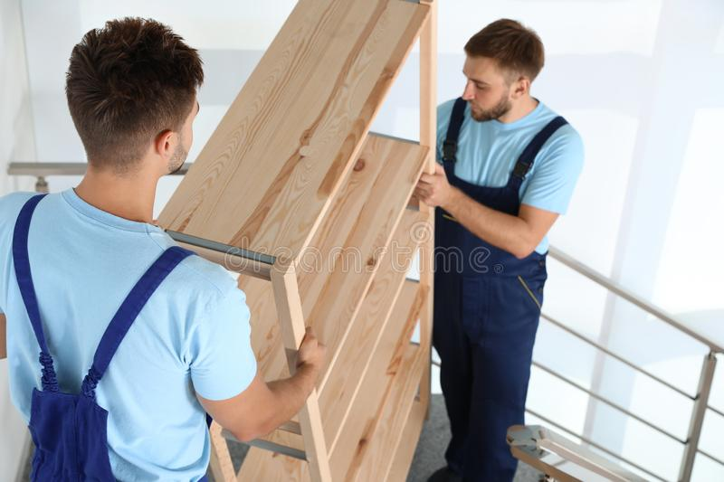 Professional workers carrying wooden  on stairs in office. Moving service stock images