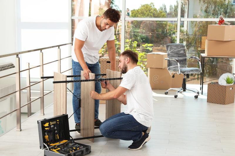 Professional workers disassembling rack. Moving service stock photos