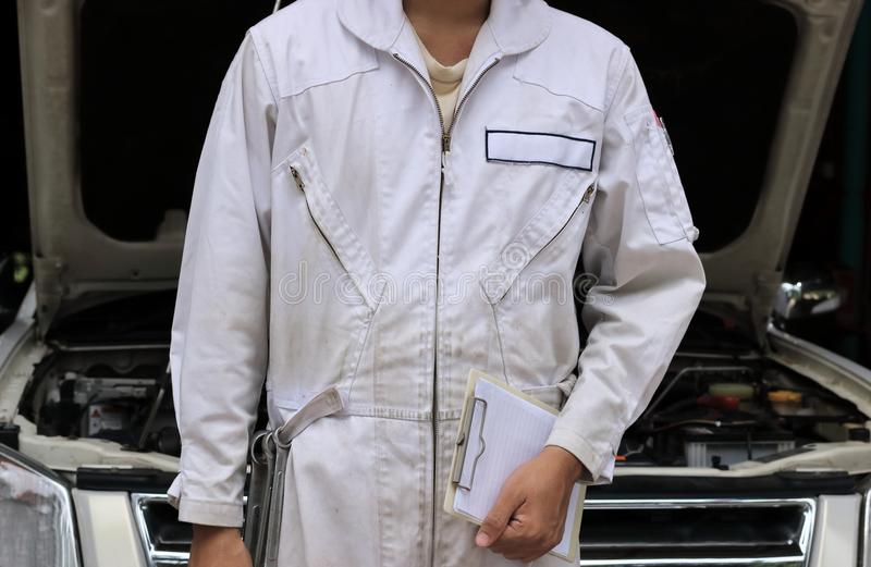 Professional young auto mechanic in uniform holding clipboard against car in open hood at the repair garage. Car insurance concept.  royalty free stock photo