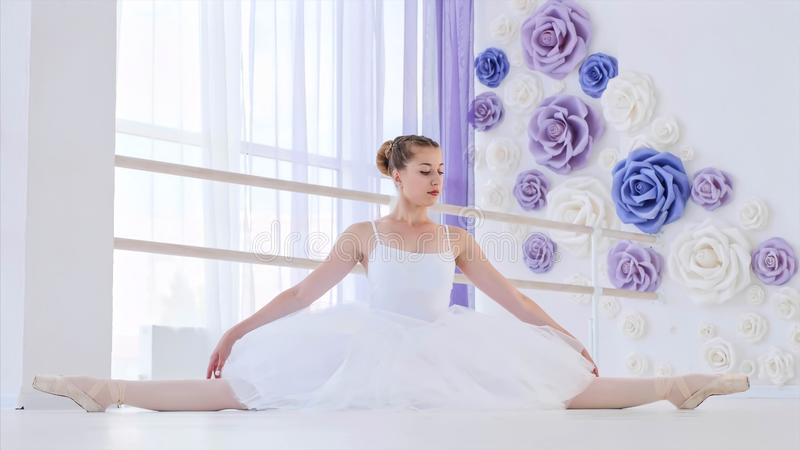 Ballerina in white tutu and pointes stretches sitting on twine in ballet class. royalty free stock images