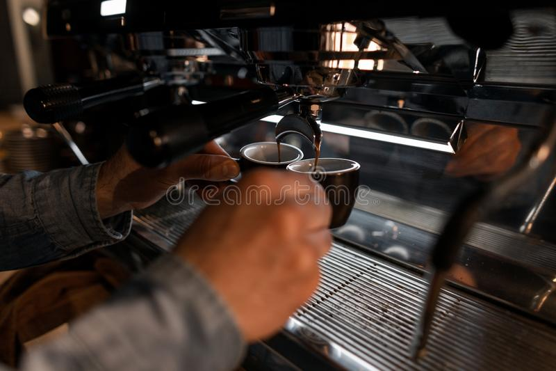 Professional young barista man in cafe prepares fragrant hot tasty espresso. Service Concept. Cups and male hands closeup. stock photo