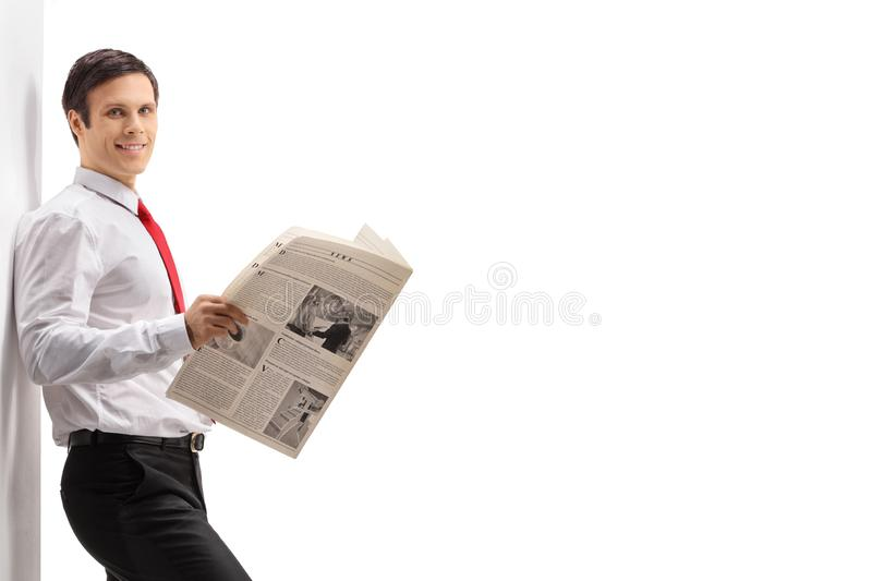 Professional young man with a newspaper leaning against a wall royalty free stock photography