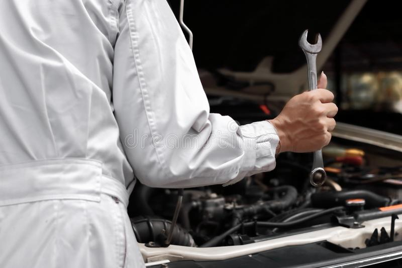 Professional young mechanic man in uniform holding wrench with open hood at the repair garage. Car insurance concept. Professional young mechanic man in uniform royalty free stock image