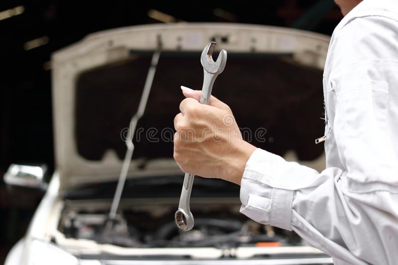 Professional young mechanic man in uniform holding wrench with open hood at the repair garage. Car insurance concept. Professional young mechanic man in uniform stock photography