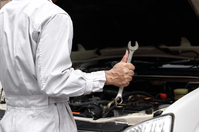 Professional young mechanic man in uniform with wrench diagnosing engine against open hood at the repair garage. Car insurance con. Cept stock photos