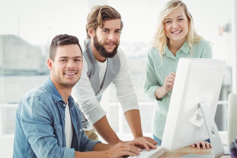 Professionals discussing at computer desk royalty free stock image