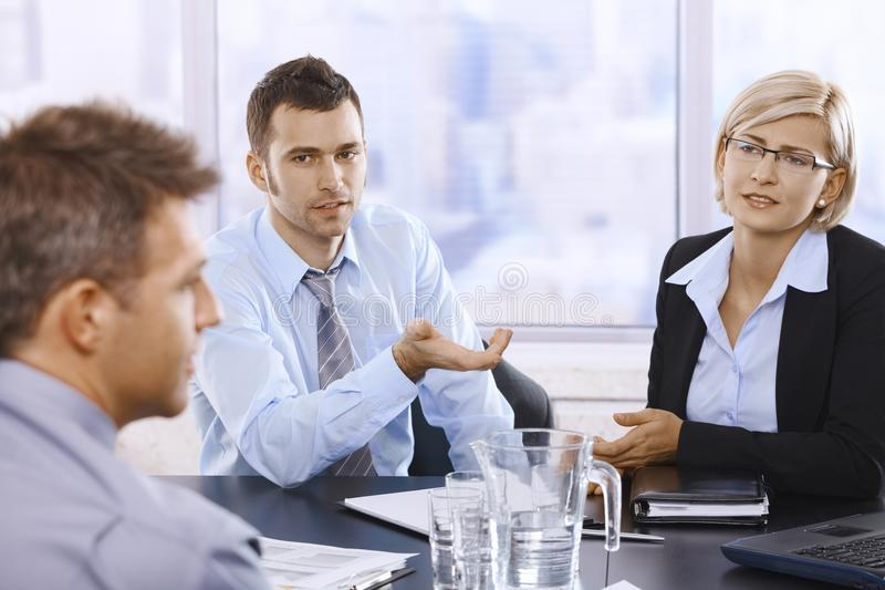 Professionals at discussion. Professionals sitting at meeting table, discussing work problems in skyscraper office stock images