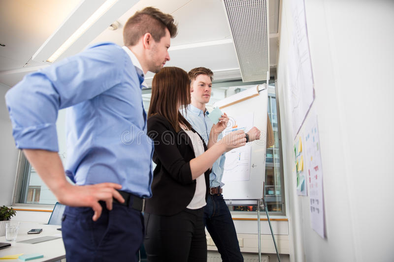 Professionals Looking At Plans Stuck On Wall In Office royalty free stock photo