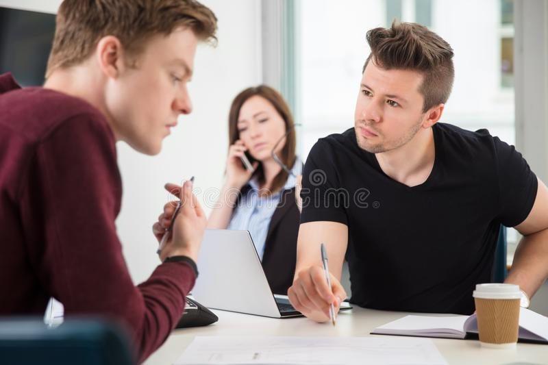 Professionals Planning While Colleague Using Mobile Phone In Off stock image