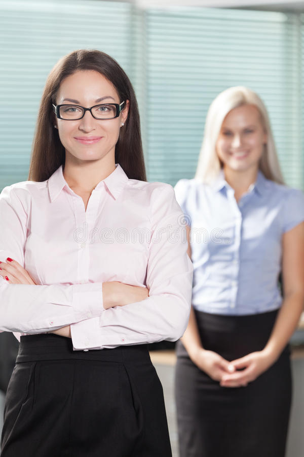Professionals. Two beautiful and confident business ladies on the office stock images