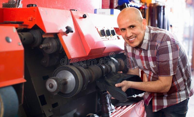 Professioneel bekwaam vakman oppoetsend schoeisel op machine stock fotografie