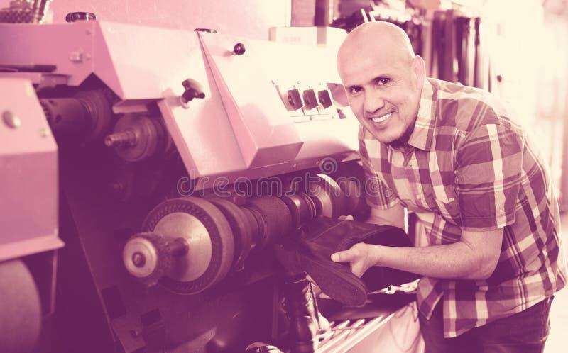 Professioneel bekwaam vakman oppoetsend schoeisel op machine stock foto's