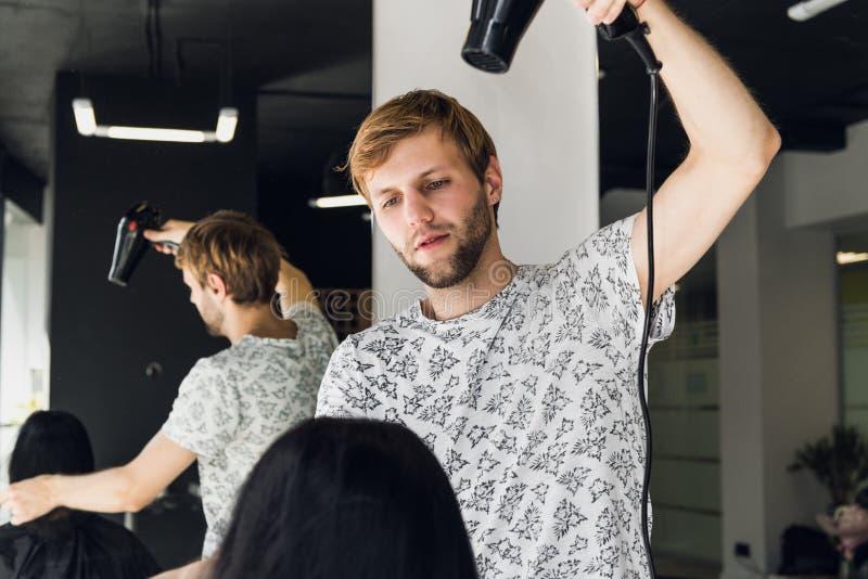 Professioneel het glimlachen mannelijk drogend de vrouwen` s haar van de stilistslag met een droger in salon stock afbeeldingen