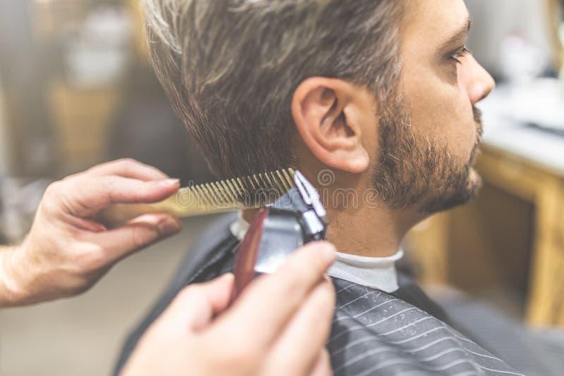 Professioneel kapper het stileren haar van zijn cliënt door kam en clipper te gebruiken royalty-vrije stock afbeeldingen