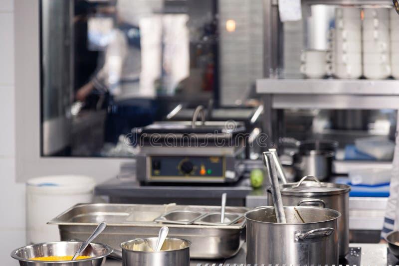 Professioneel keukenrestaurant Keukengerei, plaat met metaalpotten met deksels en lepels De voorwaarden van de ?onceptschending e royalty-vrije stock fotografie