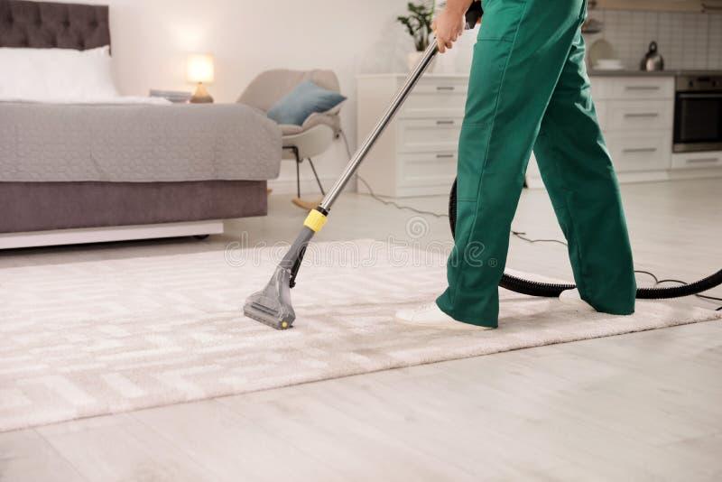 Professioneel portier schoonmakend tapijt binnenshuis stock fotografie