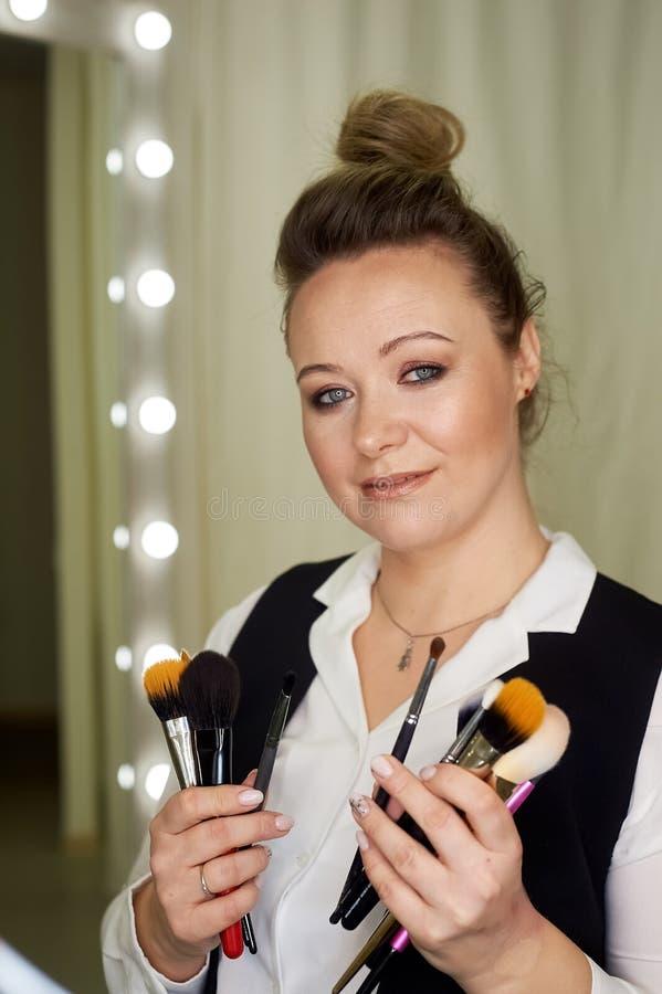 Professioneel portret van stilist en make-upkunstenaar met borstels Het creatieve werk in de schoonheidsindustrie stock foto