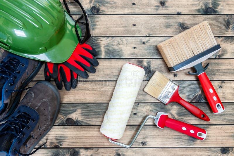 Professioneel schilder, hulpmiddelen en het werkmateriaal op houten achtergrond stock afbeeldingen