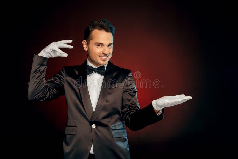 Professionele Activiteit Impresario in kostuum en handschoenen status geïsoleerd op muur die truc tonen die speelse camera kijken stock fotografie