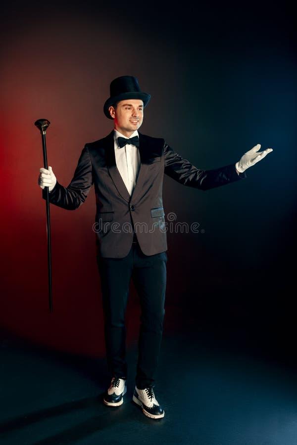 Professionele Activiteit Impresario in van de kostuumhandschoenen en hoed status geïsoleerd op muur met riethanden die opzij het  stock foto's