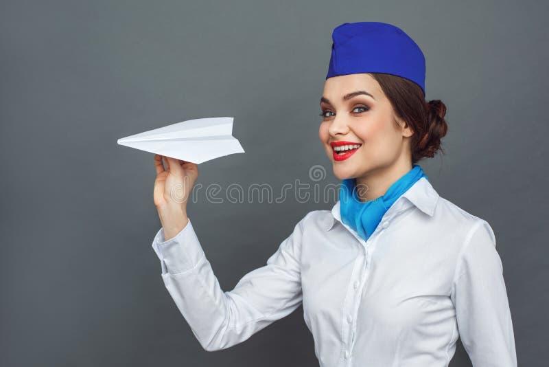 Professionele Activiteit Stewardess die bij het grijze spelen met document vliegtuig speels glimlachen wordt zich geïsoleerd bevi royalty-vrije stock foto