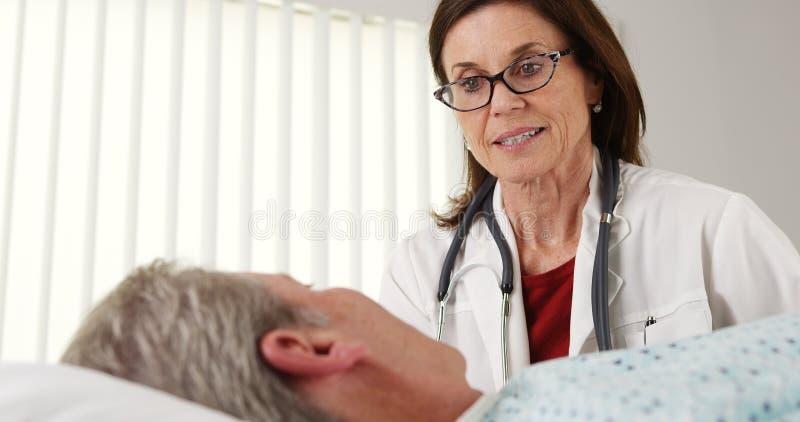 Professionele arts die aan bejaarde patiënt in bed spreken stock fotografie
