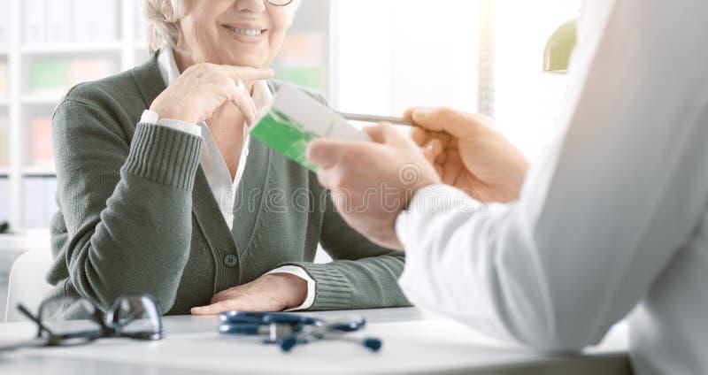 Professionele arts die een voorschriftgeneeskunde geven aan een hogere patiënt royalty-vrije stock foto