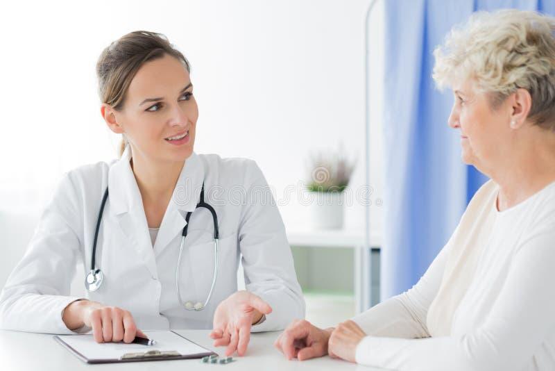 Professionele arts die pillen adviseren stock afbeelding