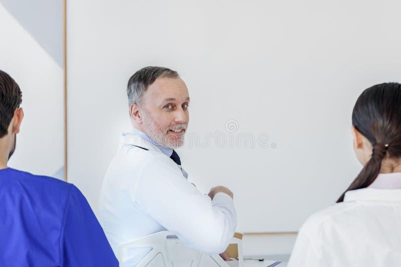 Professionele artsen die aan interessant rapport luisteren stock foto