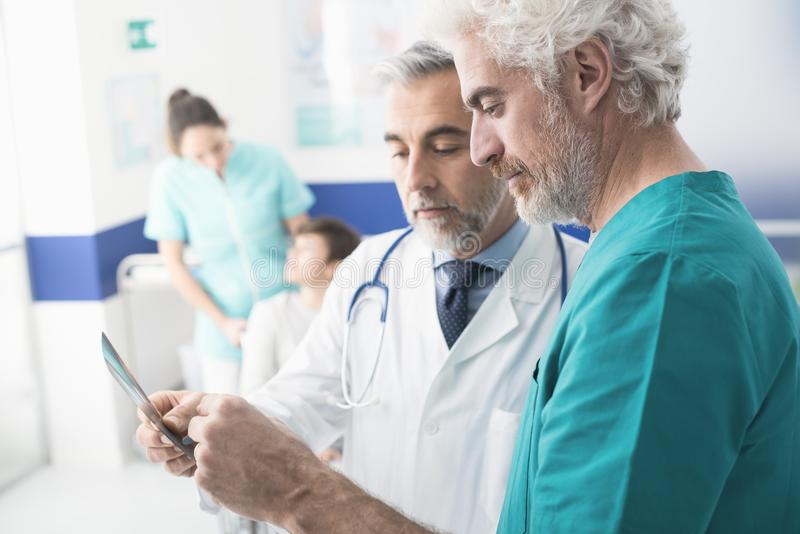 Professionele artsen die de geduldige röntgenstraal van ` onderzoeken s royalty-vrije stock foto's
