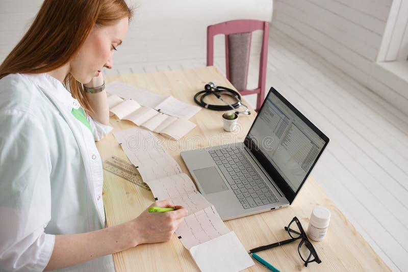 Professionele artsencardioloog of neuroloog die een cardiogram van patiënten analyseren en medische dossiers op laptop schrijven stock afbeeldingen