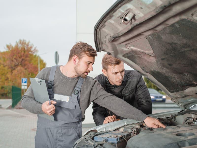 Professionele autowerktuigkundige die iets in de open kap buiten tonen aan cliënt stock foto