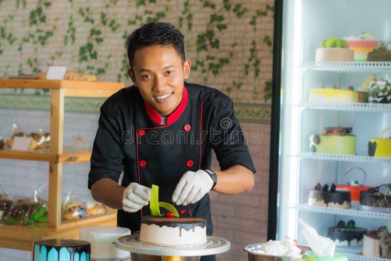 Professionele Aziatische gebakjechef-kok die cake verfraaien die rode kers zetten royalty-vrije stock foto's
