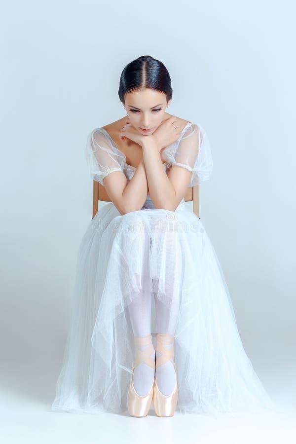 Professionele ballerinazitting met haar balletschoenen op de grijze achtergrond stock foto's