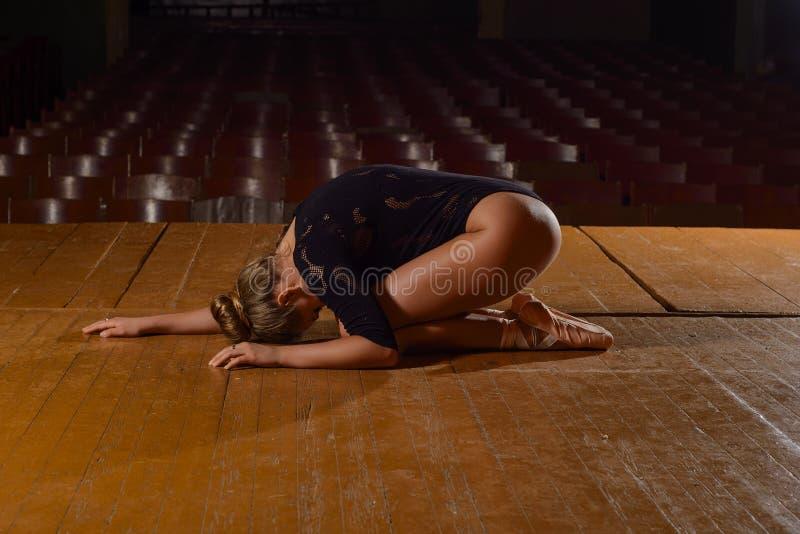 Professionele balletdanser die op het stadium na de prestaties liggen stock afbeelding