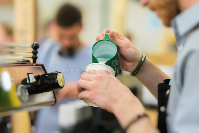 Professionele barista, die bij de bar, pourinmelk in document kop met koffiecappuccino werken Het professionele koffie maken royalty-vrije stock foto