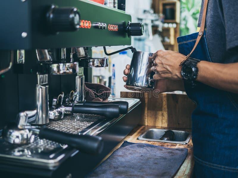 Professionele barista die jeansschort dragen die melk met roestvrij staalmok stomen op de koffie van de koffiemachine stock afbeeldingen