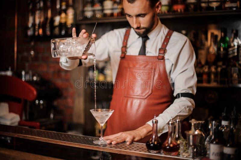 Professionele barman pourring cocktail met ijsblokjes in stock afbeelding