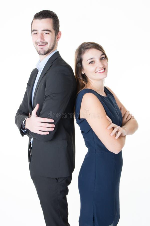 Professionele bedrijfsman en vrouw die zich rijtjes in bureau die camera met zekere gekruiste glimlachenwapens kijken bevinden stock afbeelding