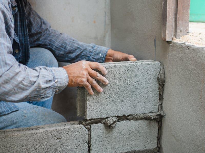 Professionele bouwvakker die bakstenen met cement leggen stock foto's