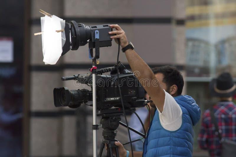 Professionele cameraman die een video op de straat schieten stock afbeelding