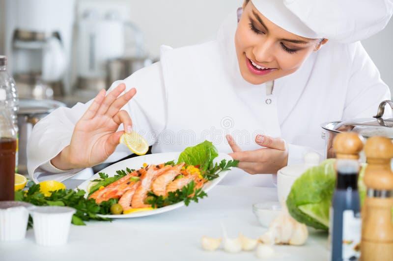 Professionele chef-kok die gebakken regenboog verfraaien stock afbeeldingen