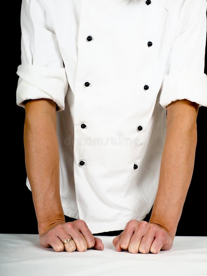 Professionele chef-kok die stevig op een lijst leunen royalty-vrije stock foto's