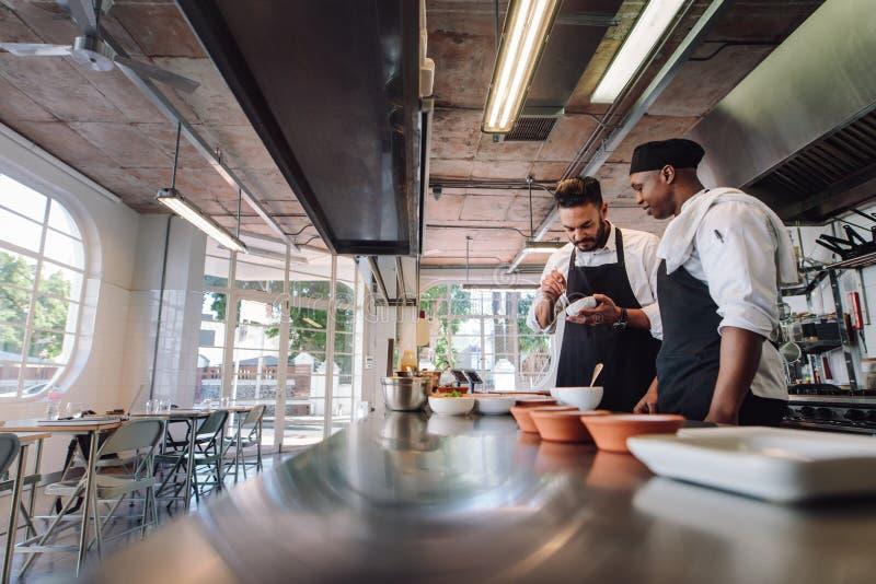 Professionele chef-koks die bij restaurantkeuken werken stock foto's