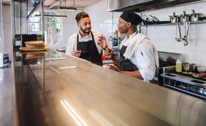 Professionele chef-koks die de smaak van nieuwe schotel in keuken bespreken royalty-vrije stock afbeeldingen