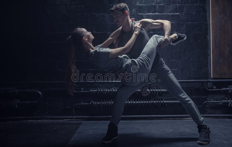 Professionele dansers die in de donkere aangestoken ruimte presteren stock foto
