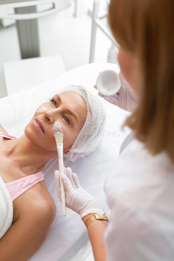 Professionele deskundige cosmetologist die een gezichtsmasker toepassen royalty-vrije stock foto