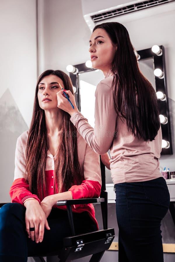 Professionele deskundige make-upkunstenaar die een borstel houden stock fotografie