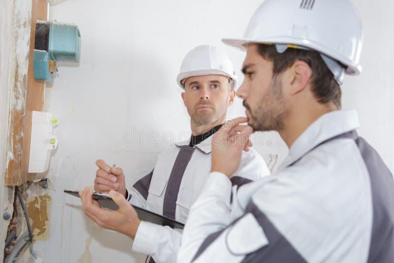 Professionele elektricien die componenten installeren in elektroschild royalty-vrije stock foto's