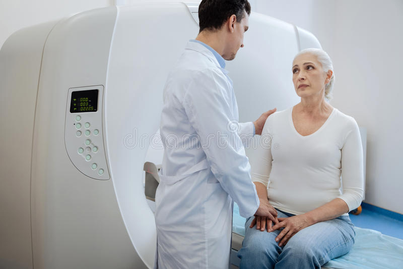 Professionele ervaren oncoloog ondersteunend zijn patiënt stock fotografie